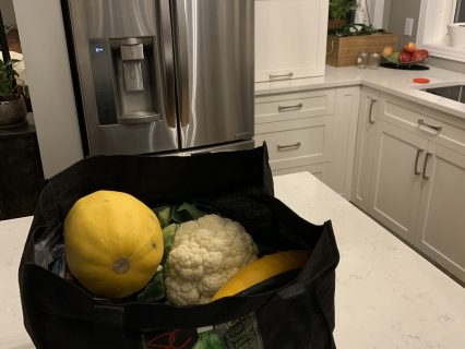 Fresh vegetables sitting on a kitchen counter in a reusable bag.