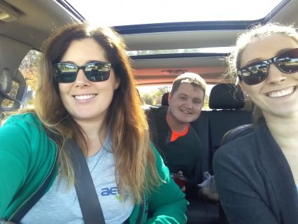Two women and a man carpooling together and leaning in to smile for a picture.