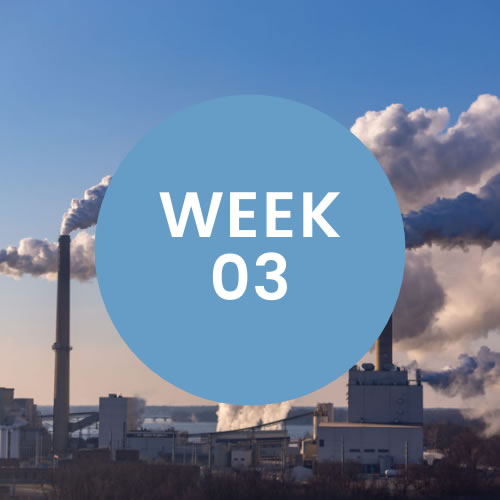 """Industrial buildings with smoke blowing from the top. A blue circle with """"Week 03"""" is in center of photo."""