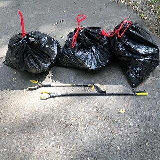 Three trash bags and trash collecting tools.
